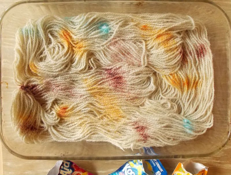 Sprinkle the Kool Aid Powder on the damp wool yarn